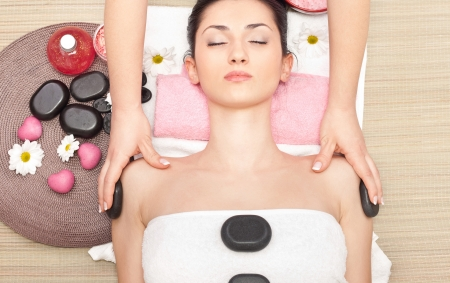 hot girl lying: hot mineral stone treatment at spa salon, top view Stock Photo