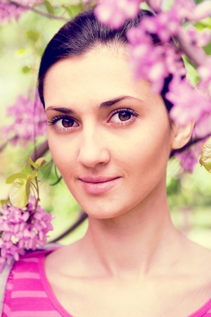 young beautiful woman next to blooming tree with violet flower, close up photo