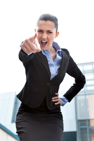 angry boss:  angry businesswoman looking and pointing upset at camera, standing outdoor front office building  Stock Photo