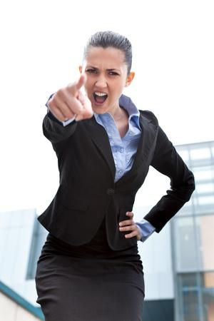 jefe enojado:  Empresaria enojada mirando y apuntando molestos ante la cámara, permanente edificio frente al aire libre