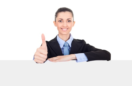 thumbs up sign: Successful businesswoman with thumbs up and white sign, smiling friendly, young beautiful woman behind blank white billboard