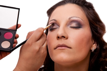 Portrait of attractive young woman applying eyeshadow with blusher photo