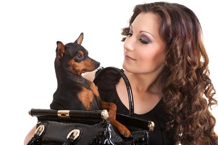 mujer con perro: Mujer joven con un perro pequeño, que está vestido con un traje negro, sobre fondo blanco Foto de archivo