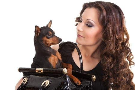 young woman holding a small dog, he is dressed in a black  dress, isolated on white background photo