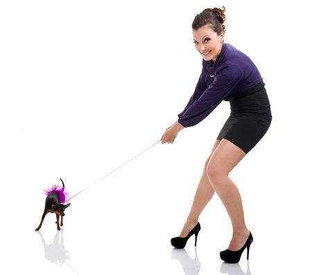 girl pulling miniature pinscher  on leash, isolated on white background Stock Photo - 10274920