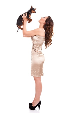 attractive girl plying with  her little dog, isolated on white background photo