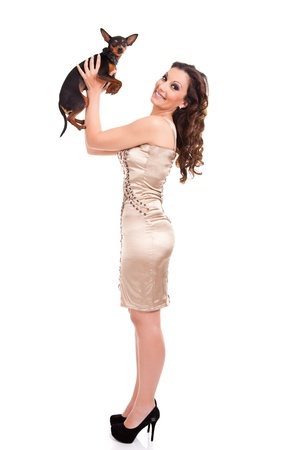 sexy, fashion woman plying with  her little puppy, miniature  pincher, isolated on white photo