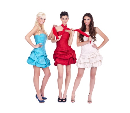 three girls in trendy fashion dresses on white background