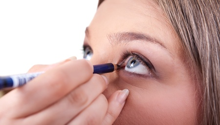 make-up artist applying make-up on eyes with eyebrow pencil, close up photo