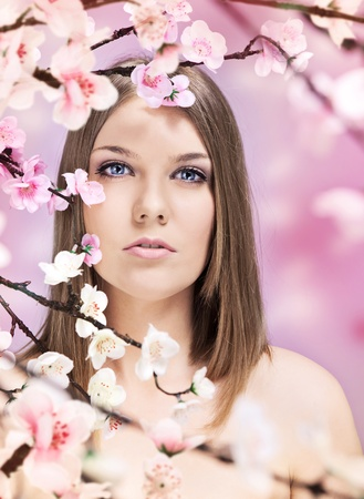 surrounded: beautiful woman surrounded by blossoming flowers Stock Photo