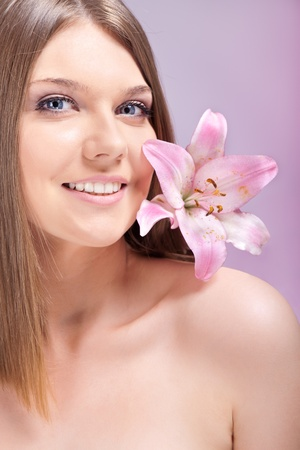 young beautiful woman with pink lily on shoulder photo