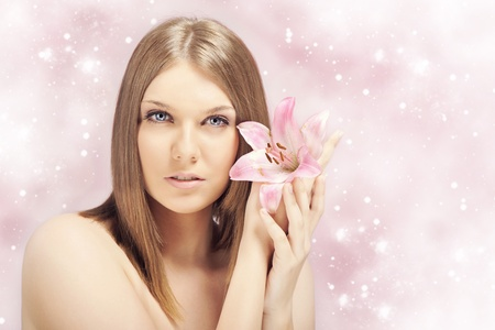 sensual spa woman with perfect skin holding pink lily photo