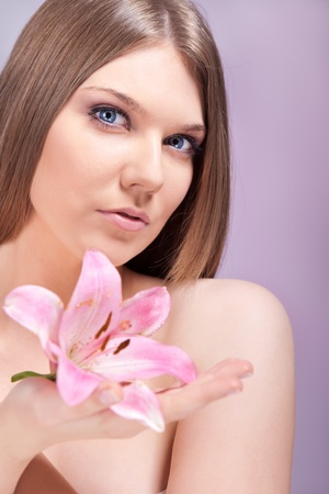 young sensual woman holding pink lily, healthy spa photo