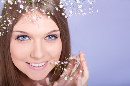 beautiful young woman with white flowers, looking at camera photo