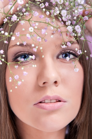 beautiful woman face with flowers, close up, pearls in hair as wedding decoration photo