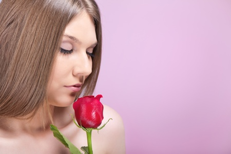young woman enjoining in smell of red rose photo