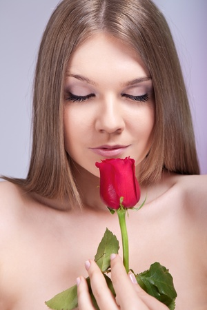 Beauty young girl enjoying in smell of red rose Stock Photo - 10275159