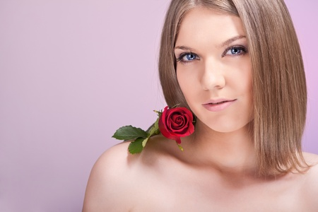 Beautiful woman with red rose on shoulder, looking at camera photo
