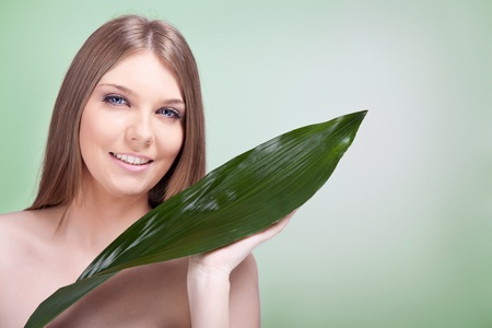 woman satisfied with her skin, smiling and holding green leaf photo