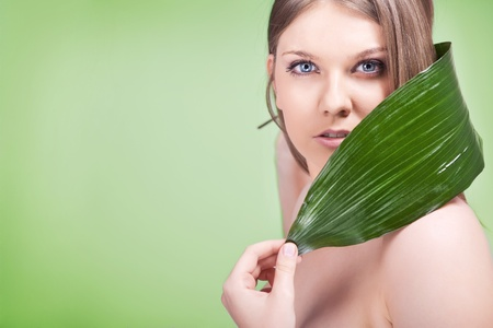 young  woman with green leaf on shoulder, concept - healthy skin photo