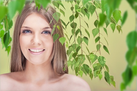 Beautiful young woman with leaves photo