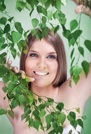 beauty girl between lot of green leaves photo