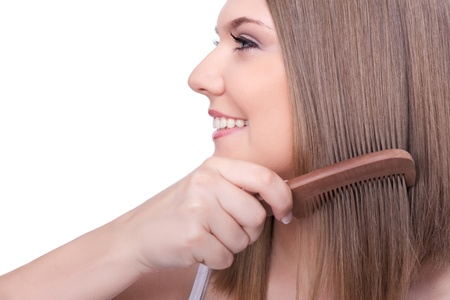 combing hair: young beautiful woman combing her long straight healthy hair, isolated on white background