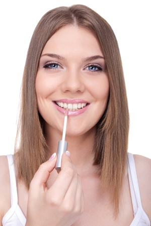 young woman applying lip gloss, smiling and looking in camera photo