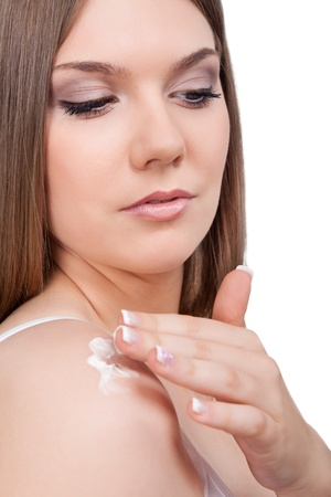 young woman applying cream on her shoulder, close up, isolated on white background photo