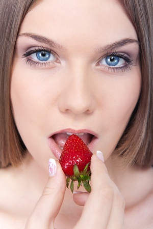 beautiful  womans face  with red strawberry next to lips, white studio background photo