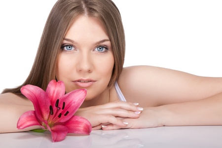 young beautiful woman relaxing with pink  flower at spa isolated on white background photo