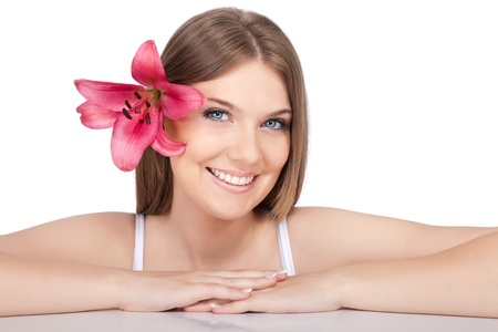 beautiful smiling girl with pink lily in hair, isolated on white background photo