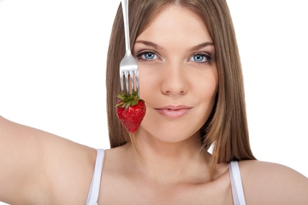 young woman showing strawberry on fork, isolated on white background photo