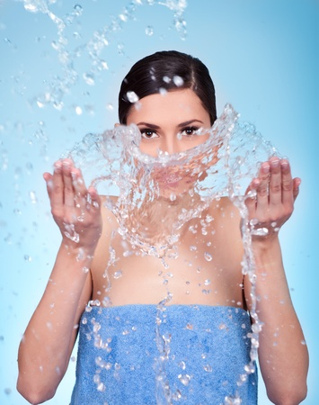 young female wash her face with water photo