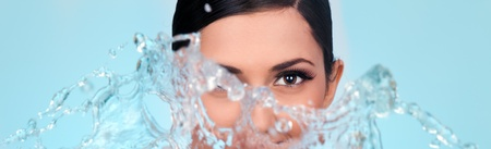 womans face with splash water on blue background photo