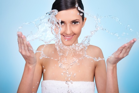 portrait of beautiful , young woman washing her face photo