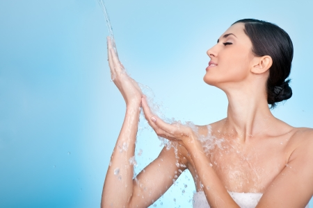 young woman enjoying in water splash on her hands photo