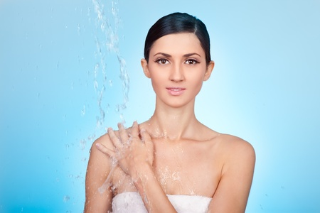 woman under stream of water falling on her shoulder on blue background photo