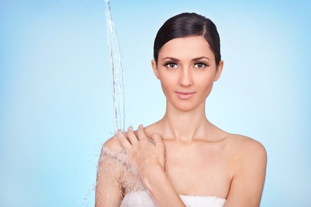 beautiful healthy woman under stream of water falling on her shoulder on blue background photo