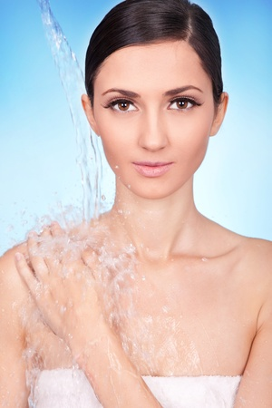 Beautiful woman with clean face and stream of water photo