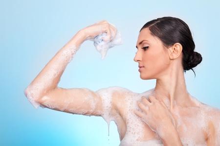 bodycare:  woman in soap foam washing her body