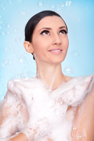 beautiful necked  woman  in foam and bubbles on blue background photo