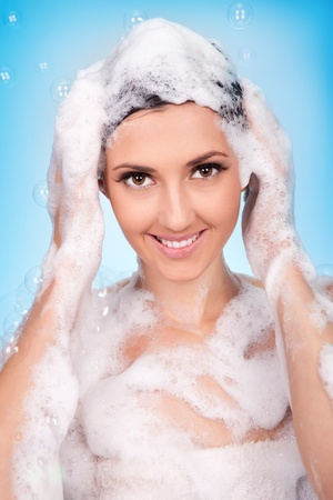 Young woman washing hair in shower   with loot of foam photo