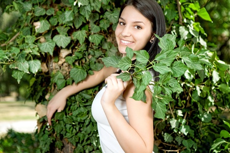 Beautiful young  girl posing near the green tree on nature Stock Photo - 10275079
