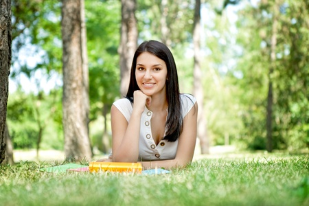 beautiful girl reading a book and relax in the park photo
