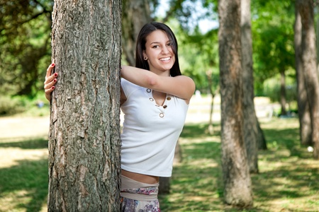 Beautiful young woman in park playing peekaboo Stock Photo - 10275146