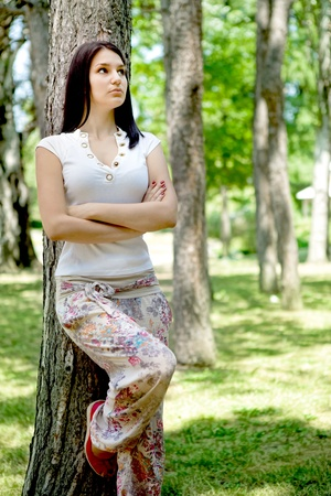 young woman near tree in park thinking Stock Photo - 10278994