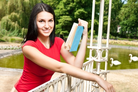 young woman reading book in the park in front lake photo
