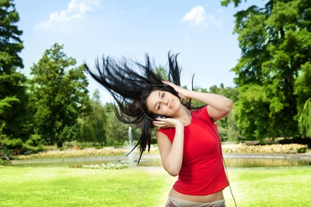 flying hair:  young woman playing and listening music with flying hair in park Stock Photo