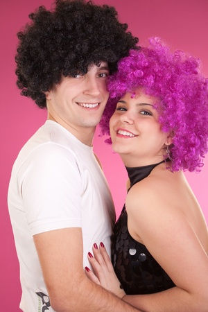 smiling disco couple with afro wigs photo
